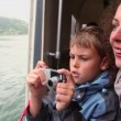 Mother with son float at passengers vessel, boy makes photo — Stock Video