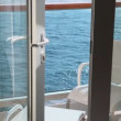 Stock Video: Door to balcony with furniture on vessel which floats in sea
