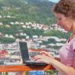 Woman pushes buttons on netbook at deck of ship in port — Stock Video