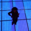 Stock Video: Womdances at dark discotheque with illuminated floor