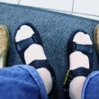 Stock Video: Mans feet in summer shoes and old pair stand near on carpet