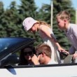 Students with kids sit in cabriolet, boys talk by hand radio — Stock Video