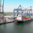 Stock Video: Machines ride and shipment of barge with containers by crane