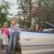 Two kids eats bread near cabriolet, parents sit in cabriolet — Stock Video