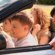 Kids sit on parents lap in cabriolet at sunny summer day — Stock Video #32346399