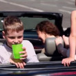 Kids with their parents sit in cabriolet and boy drinks — 图库视频影像