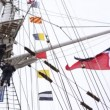 Two sailors stand above on ship mast near hanging flags — Stock Video