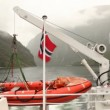 Stock Video: View from stern of vessel floating down fiord on mountain around