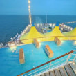 Sunbeds near pool and tents on deck of ship which float in sea — Stock Video