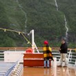 Stock Video: Several people stand on deck of vessel which float near mountain