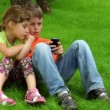Two kids sit together, boy plays with digital game on cell phone — Stock Video
