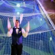 Bartender juggles by four bottles at background of pool with net — Stock Video