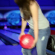 Young girl throws bowling ball to beat skittles in dark club — Stock Video #32347711