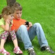 Two kids sit together at grass near tree — Stock Video