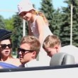 Young couple sit in cabriolet and two kids stand on back seats — Stock Video