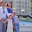 Couple and kids stand near cabriolet, boy hold girl — Stock Video #32347845