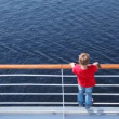 Boy looks at water standing on ship deck in afternoon — Stock Video #32347891