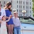 Young couple with two kids stand near cabriolet — Stock Video