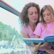 Mother reads book with kids at balcony on ship — Stock Video