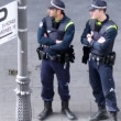 Two policemen stand on street near going people — Stock Video