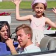 Couple sit in cabriolet, little girls wave hands at back seat — Stock Video #32348219
