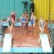 Sportswomen train synchronous jumps from springboard in pairs — Stock Video