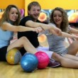 Boy and girls sit and simulate rowing on floor in bowling club — 图库视频影像