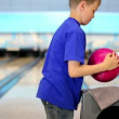 Boy takes ball and throws it to beat skittles on bowling lane — Stock Video #32348325