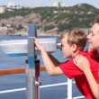 Stock Video: Boy looks in binocular on ship deck under direction of mother