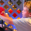 Stock Video: Boy holds red gun of video game and shoots from it