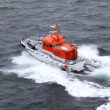 Stock Video: Saving powerboat floats on water dissecting waves in afternoon