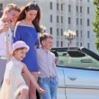 Students and two kids stand near cabriolet at sunny summer day — Stock Video