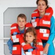 Mother with son and daughter in life jackets stands on ship deck — Stok video