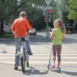 Boy sits on bicycle and his sister stands at pedestrian crossing — Stock Video #32349643