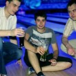 Three friends sit and drink bear in dark bowling club — Stock Video