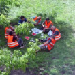 Group of workers in uniform sit in ring at picnic on grass — Stock Video