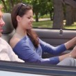 Girl rotate wheel in cabriolet and boyfriend is near — Stock Video
