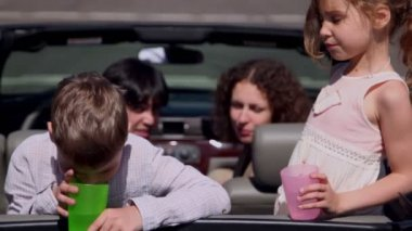 Parents sit in cabriolet and watch their kids with glasses — Stock Video