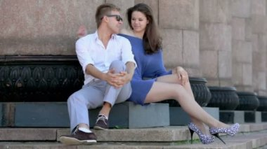 Young couple sit on steps near colonnade, fluff flies around — Stock Video