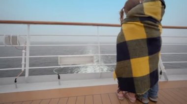 Kids wrapped in plaid stand on deck and admire seascape — Stock Video