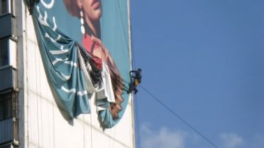 Worker dismantles banner hanging highly on house wall — Stock Video