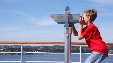 Boy looks in binocular on ship deck against blue sky — Stock Video