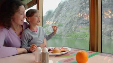 Mother and daughter sit at table with food and watch mountain — Stock Video