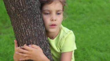 Little girl embraces tree and speaks, closeup view at summer day — Stock Video