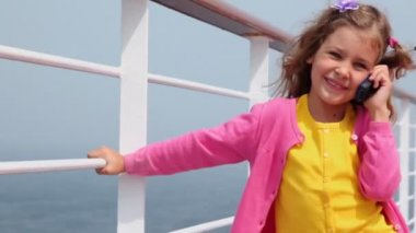 Little girl talks by cell phone and holds fence on deck — Stock Video