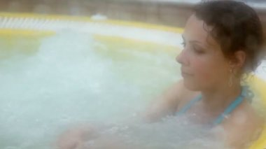 Woman sits in pool with hot water and vapor covers all around — Video Stock