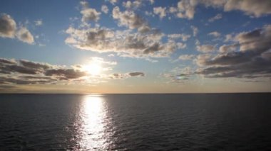 Line of horizon dividing sea and sky with sun and clouds — Stock Video