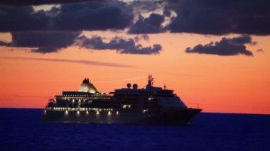 Bateau avec illumination flotteurs en mer au coucher du soleil sur ciel nuageux — Vidéo