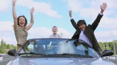 Parents and two kids stand in cabriolet and wave hands — Stock Video