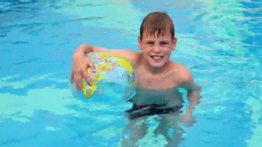 Malý chlapec stojí v bazénu a podržte nafouknutý míč — Stock video